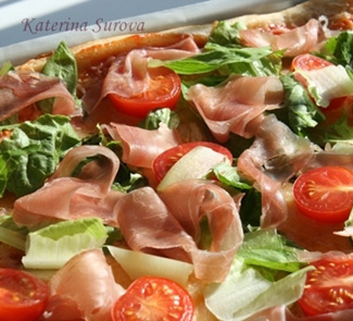 Pizza with salad and prosciutto