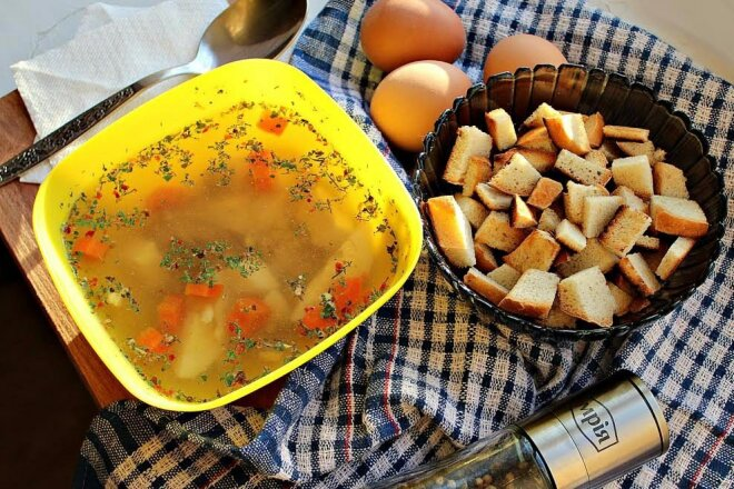 Chicken broth with egg, carrots and croutons