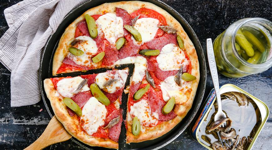 Pizza with pickled cucumbers and sausage