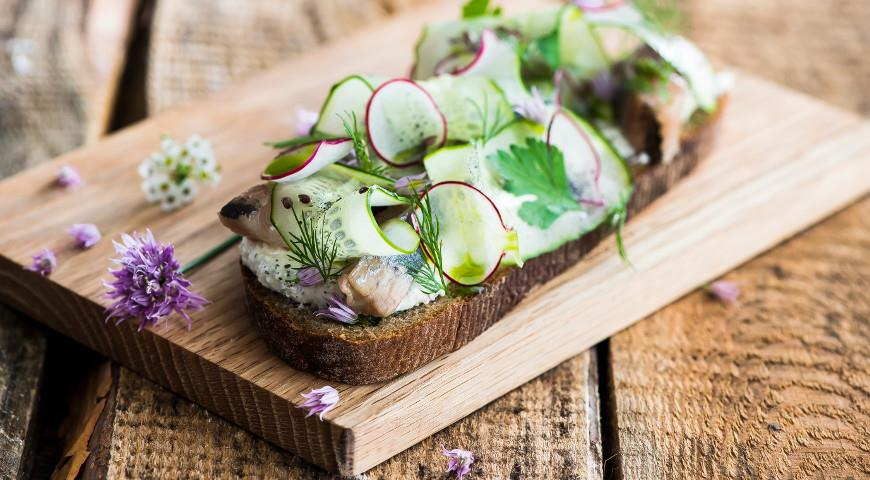 Herring on a slice of rye bread with cucumber and black salt