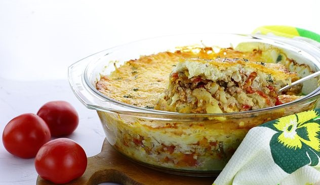 Potato casserole with minced meat, tomatoes, cheese and cream sauce
