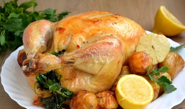 Chicken stuffed with lemon, garlic and herbs, baked with potatoes