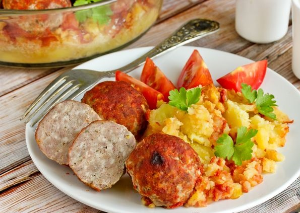 Meatballs baked with potatoes and tomato sauce
