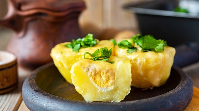 Young potatoes baked with quail eggs and cheese