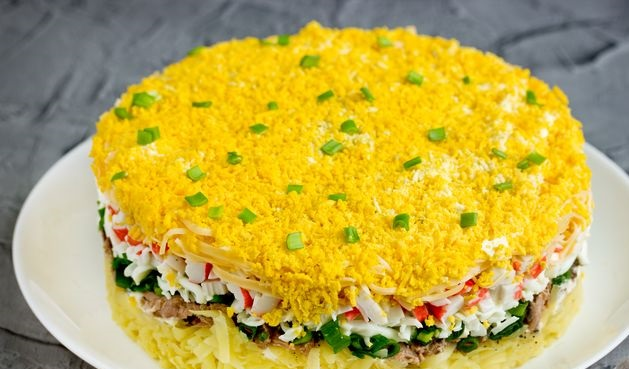 Puff salad with potatoes, tuna, crab sticks, cheese and eggs
