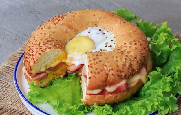 Fried eggs in a bagel with sausages and cheese
