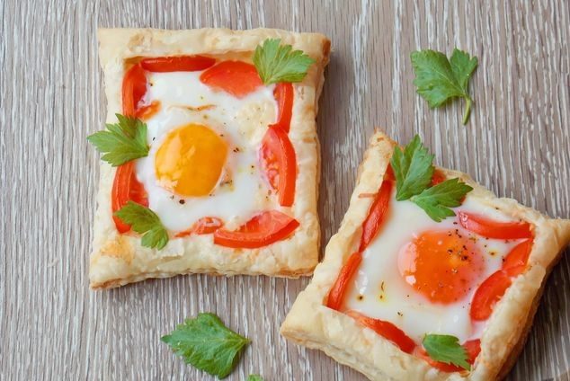 Fried eggs with cheese and tomatoes, on puff pastry