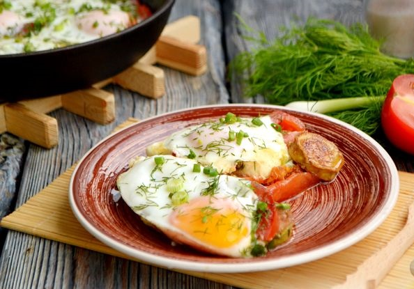 Fried eggs with zucchini, tomatoes and herbs