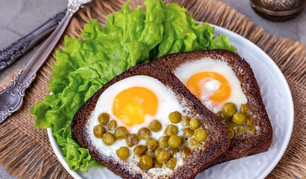 Fried eggs with canned peas in rye bread