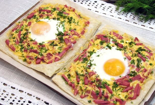 Fried eggs on puff pastry with sausage and cheese