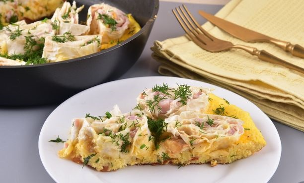 Omelet with pita bread, ham, melted cheese and tomato