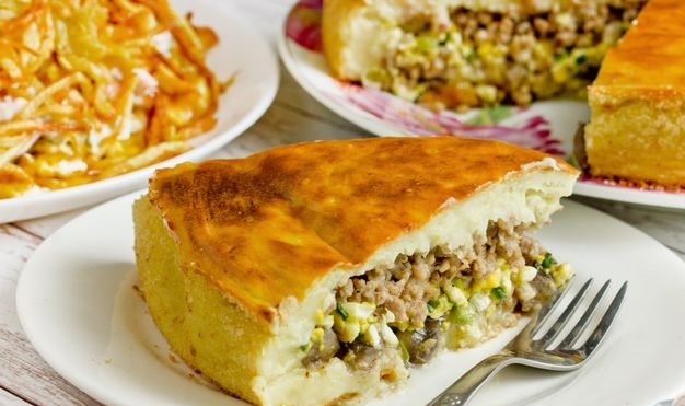 Potato pie stuffed with minced meat, mushrooms and boiled eggs with green onions