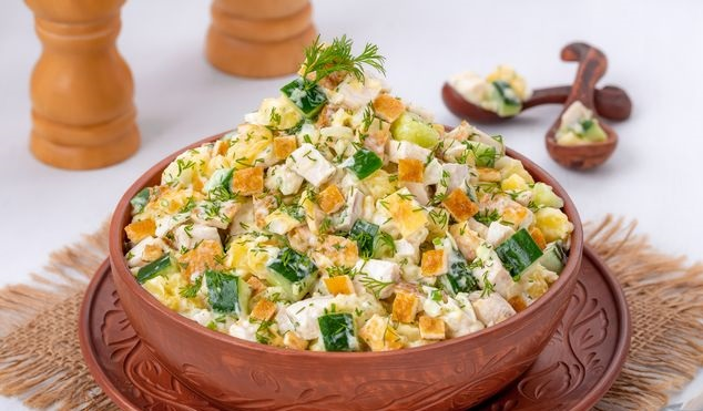 Salad with chicken, potatoes, cucumbers and egg pancakes