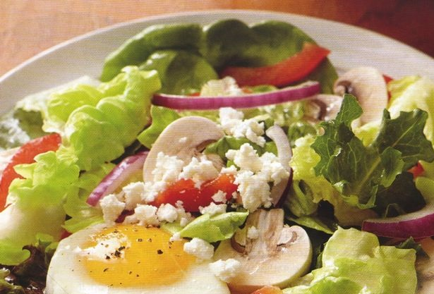 Salad with poached eggs, raw mushrooms, bell peppers and feta