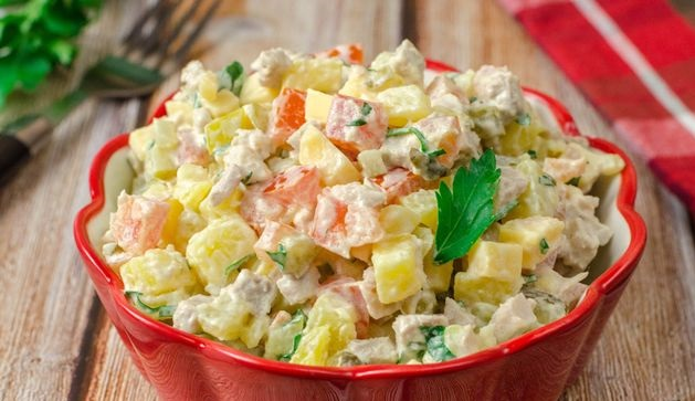 Meat salad with potatoes, tomatoes, pickles and cheese