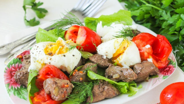 Warm salad with chicken liver, cherry tomatoes and poached egg