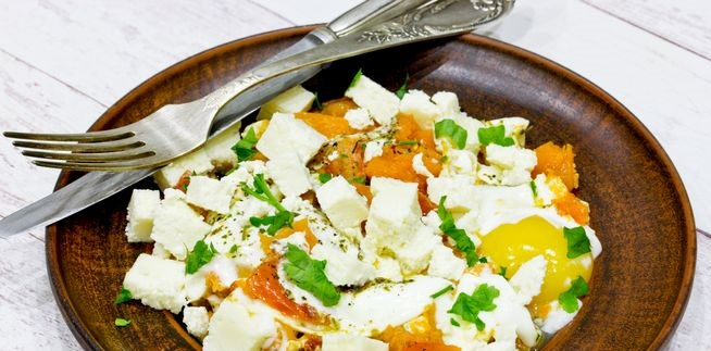 Fried eggs with pumpkin, tomatoes and feta cheese