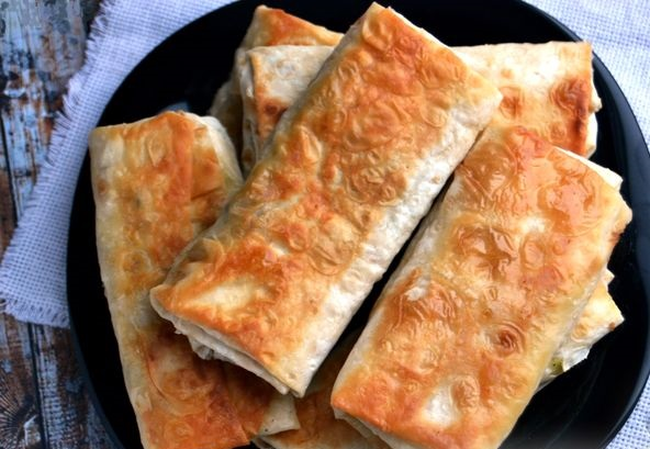 Lavash envelopes with sprats, eggs, potatoes and pickles