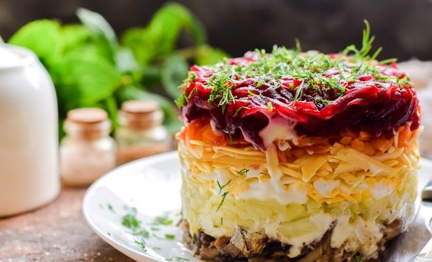 Puff salad with sprats, potatoes, beets, carrots and cheese