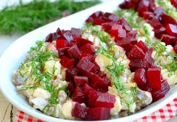 Salad with beets, herring, potatoes, melted cheese and apple