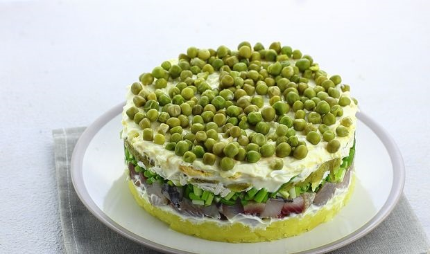 Puff salad with herring, potatoes, melted cheese and pickles