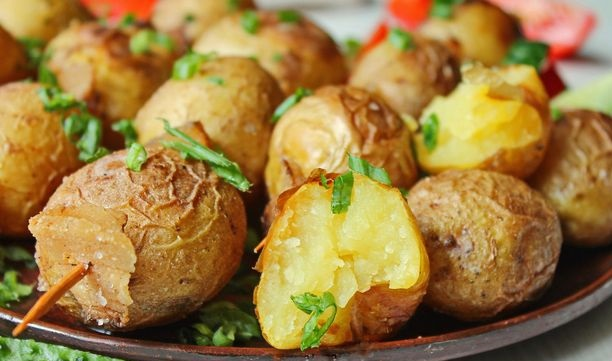 Young potatoes, baked with bacon, on skewers